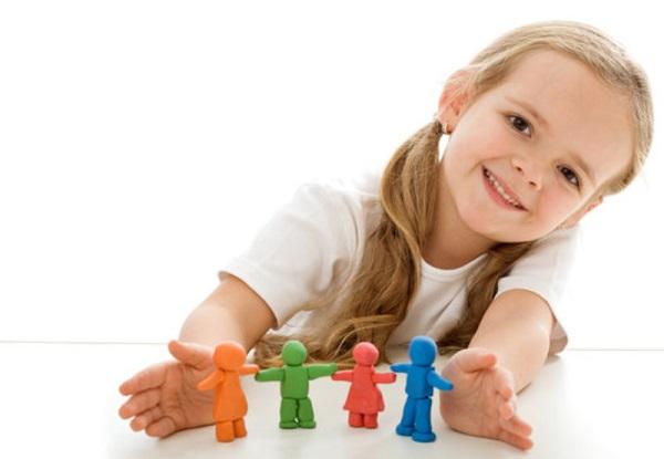 Девочка улыбается. Перед ней стоят пластилиновые фигурки