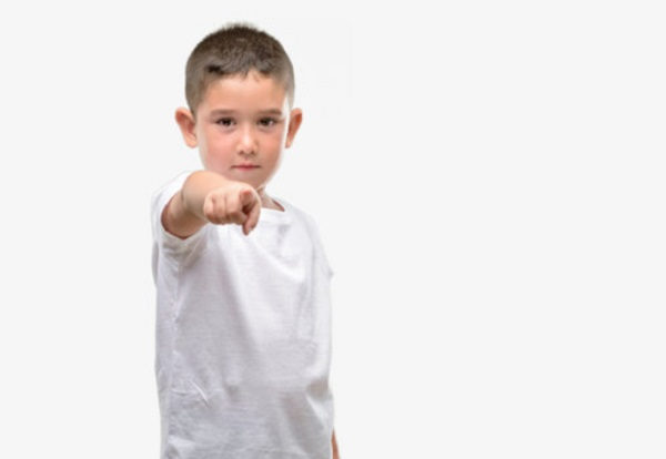 Серьезные мальчик указывает на что-то пальцем