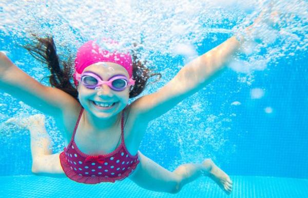 Девочка плывет под водой в бассейне