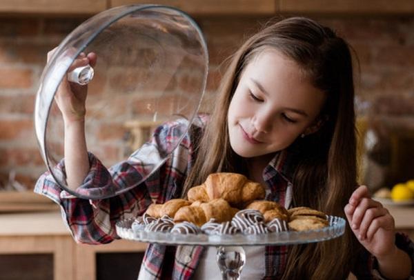 Девочка смотрит на кондитерские изделия
