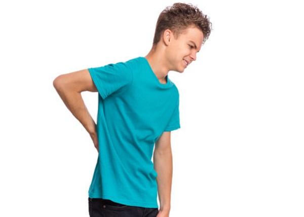 Мальчик держится за спину, которая болит