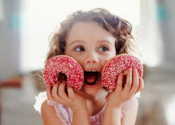 Девочка держит два глазурованных пончика в руках