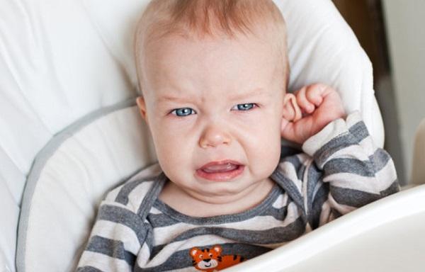 Ребенок держится за ухо и плачет