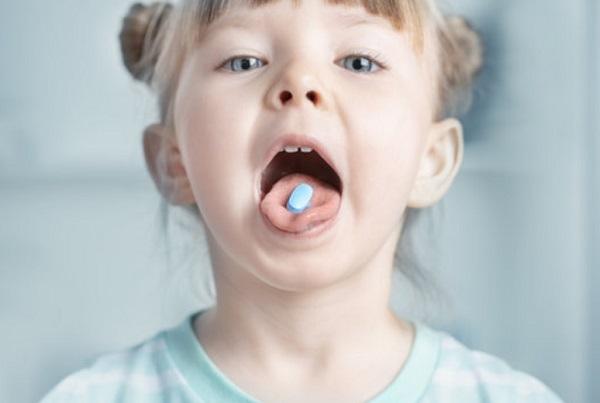 Девочка держит таблетку на языке